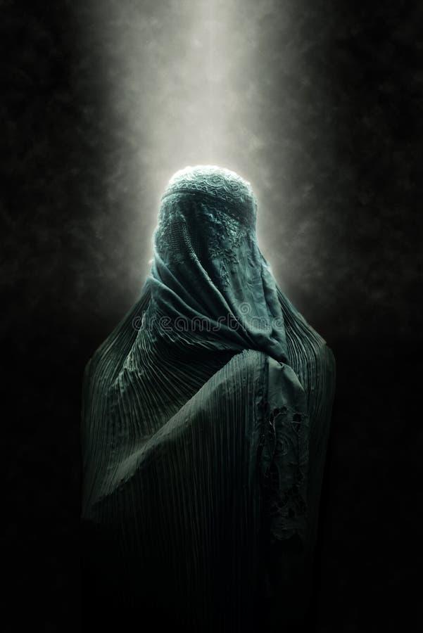 Veiled Islamic woman in a beam of light stock photos