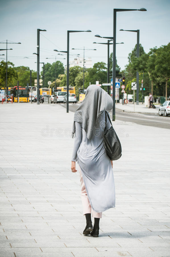 Veiled Muslim woman walking in the street near the train station stock photography