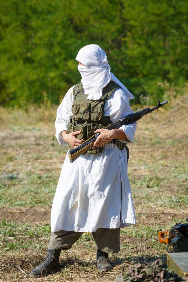 Veiled soldier in traditional islamic white clothes with the Kalashnikov gun royalty free stock photography