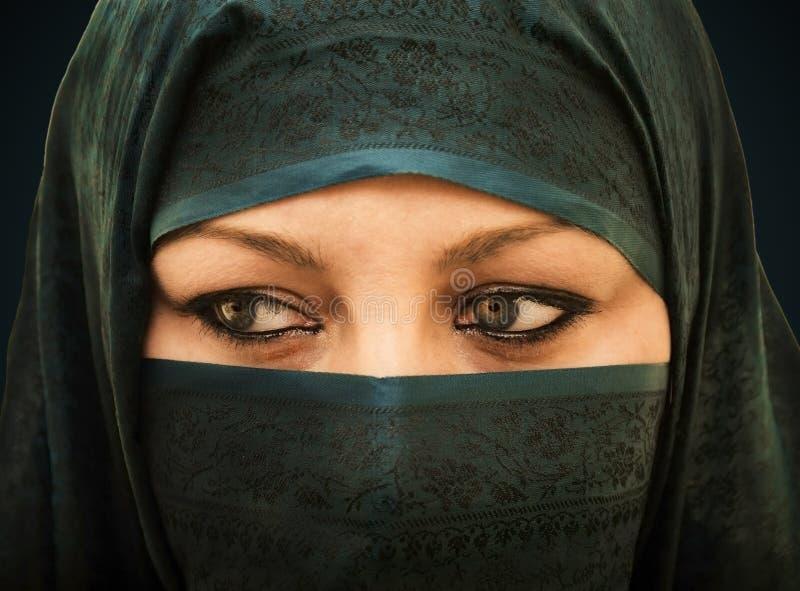 Veiled woman. Arabic veiled woman with turquoise burka stock photo