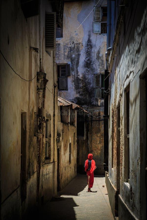 Veiled woman walking through a narrow street stock image