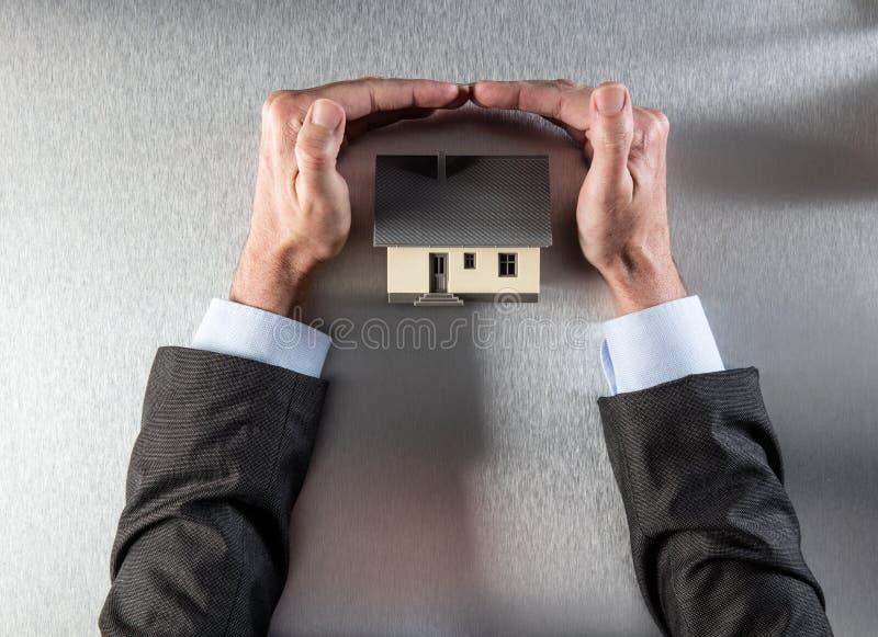 Veilig isolatiehuis met zakenmanhanden die en dak beschermen beveiligen royalty-vrije stock afbeelding