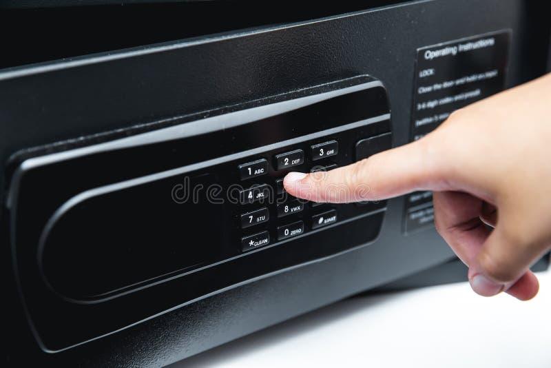 Veilige doos in hotelbediening op de kamer met hand die vinger gebruiken bij wachtwoord zeer belangrijk stootkussen stock foto