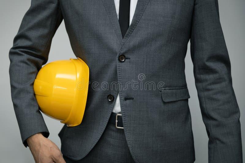 Veiligheid op het werk of bedrijfsconcept bouwnijverheid - zakenman met gele helm stock afbeelding
