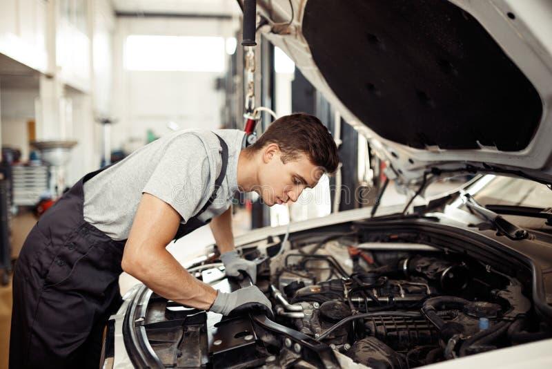 Veiligheid sirst: een knappe autowerktuigkundige controleert de motor royalty-vrije stock afbeelding