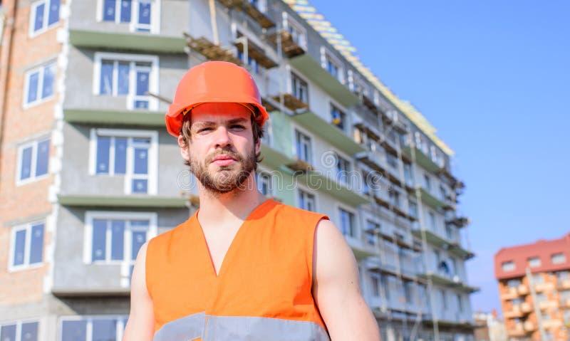 Veiligheid van bouwer bij het werkconcept Kerel in beschermende die helmtribune voor de bouw uit rode bakstenen wordt gemaakt con stock fotografie