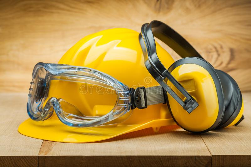 Veiligheid van het werk De hulpmiddelen van de bouwveiligheid gele helm blauwe beschermende brillen en oortelefoons op houten ach royalty-vrije stock foto's