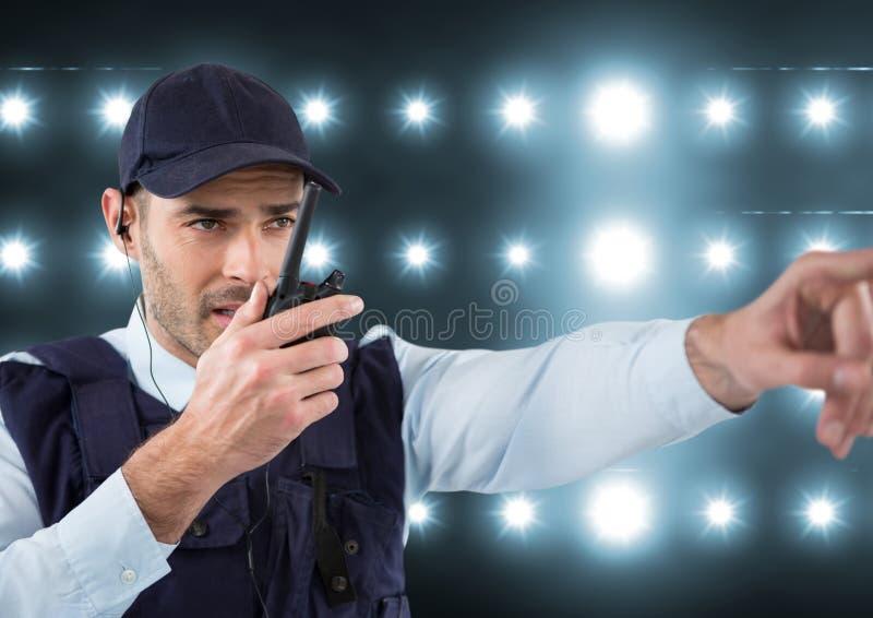Veiligheidsagent die met walkie-talkie spreken en iets in een lichte rug richten stock foto's