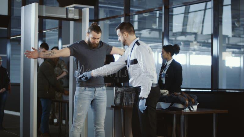 Veiligheidsagent die onderaan een mannelijke passagier tikken royalty-vrije stock afbeelding