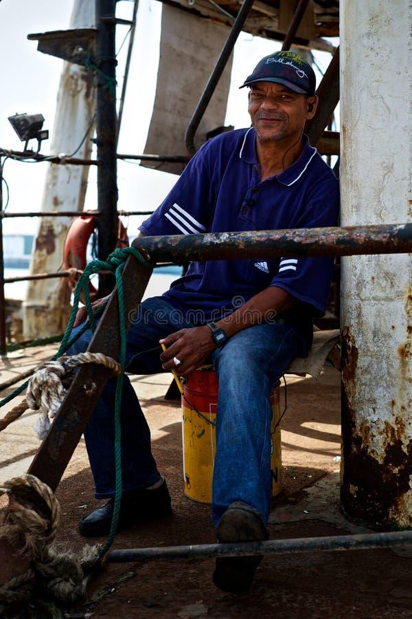 veiligheidsagent die over een vissersboot in het dok letten op stock foto
