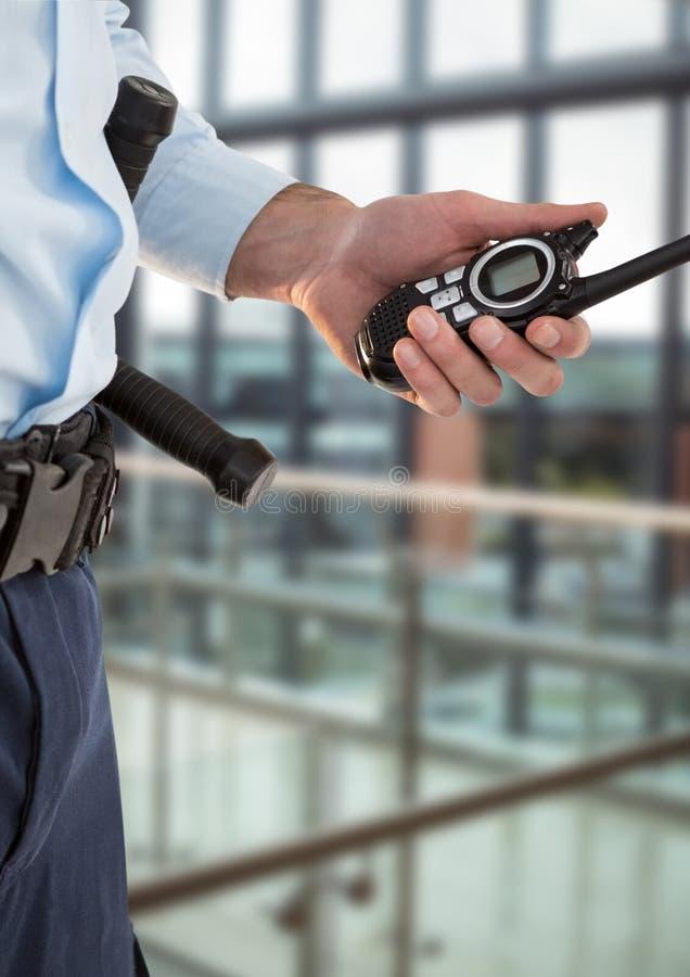 Veiligheidsagent met walkie-talkie in het bureau met een vage rug stock foto