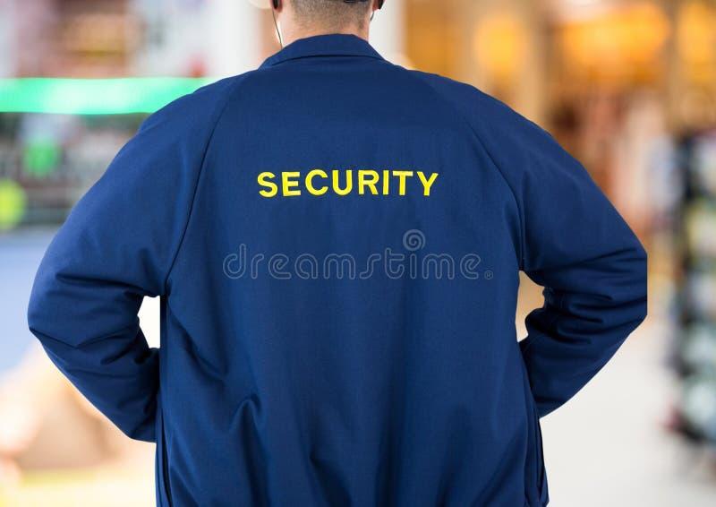 Veiligheidsagent terug op lichtenachtergrond stock afbeeldingen