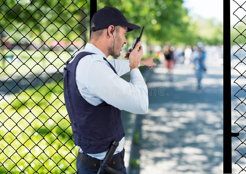 veiligheidsagent van het park die met de walkie-talkie en het punt aan iets vastspijkeren stock fotografie
