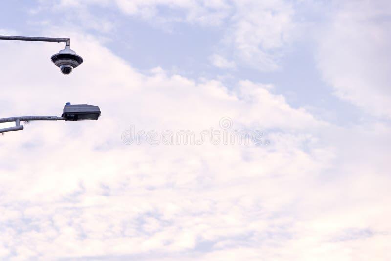 Veiligheidscamera in hemel met vele wolken bij zonsondergang met stadslamp stock foto