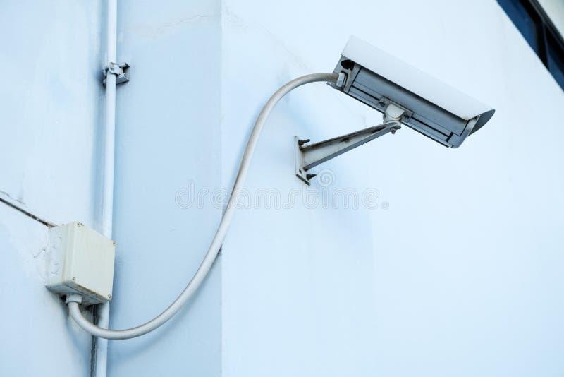 Veiligheidscamera, kabeltelevisie op de witte Technicus van de plafondplaats fixin royalty-vrije stock afbeelding