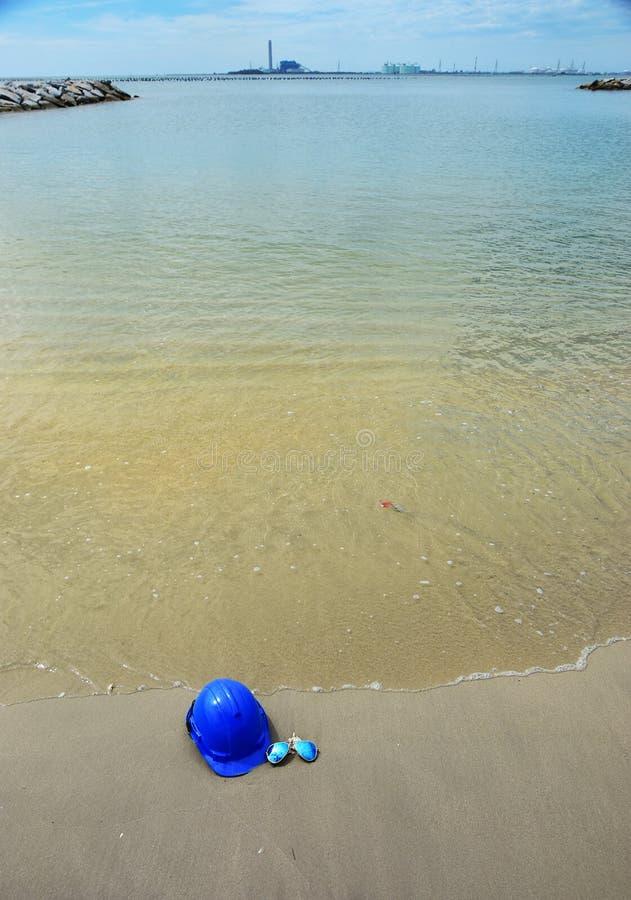Veiligheidshelm en de zonglazen op de zeegezichtachtergrond stock afbeeldingen