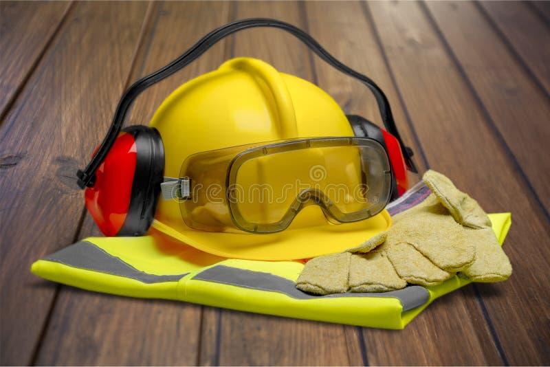 Veiligheidshelm met handschoenen, glazen, hoofdtelefoons en stock afbeeldingen