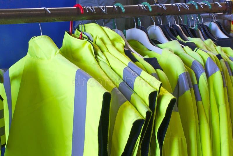 Veiligheidsjasjes op hangers stock afbeeldingen