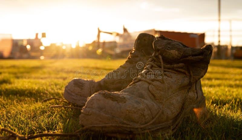 Veiligheidslaarzen bij een bouwwerf in modder voor een heldere zonsondergang wordt behandeld die royalty-vrije stock afbeeldingen