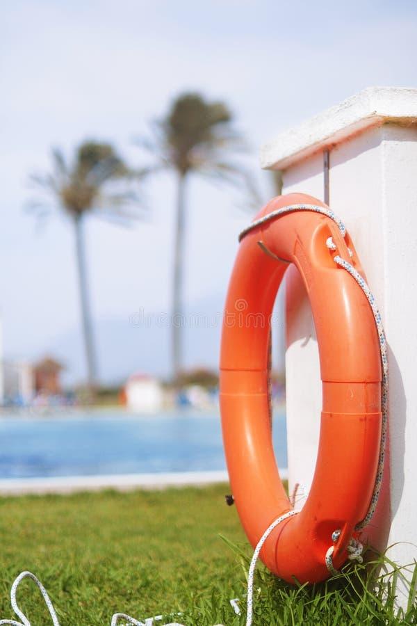Veiligheidsmateriaal, Rode de ringsvlotter die van de reddingsboeipool, ring in het verfrissen van blauw zwembad drijven Rode vlo royalty-vrije stock afbeelding