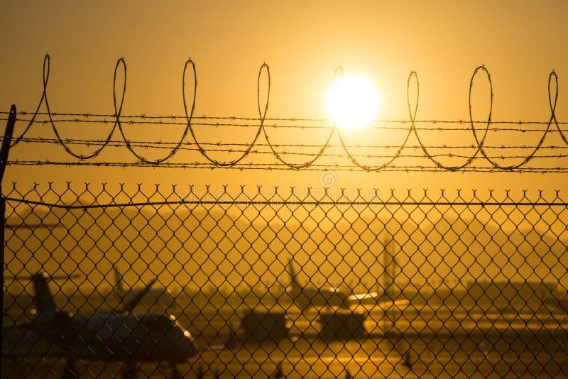 Veiligheidsomheining rond internationale luchthaven bij zonsopgang stock foto