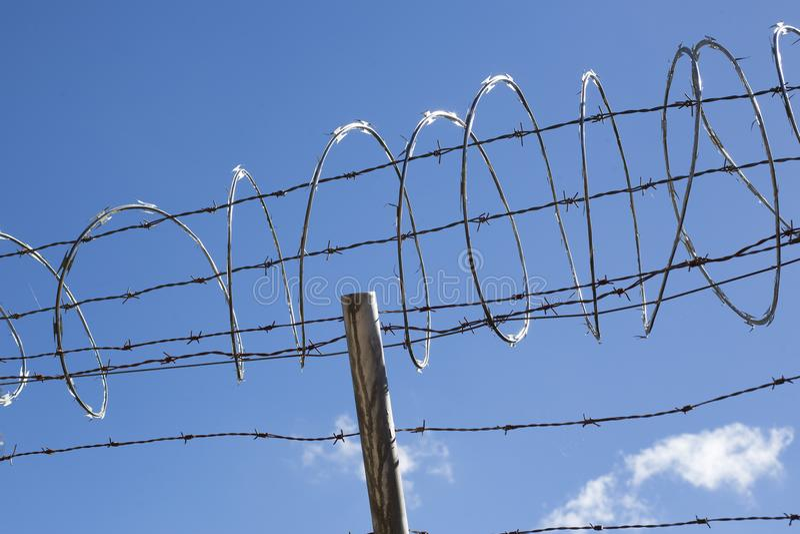 Veiligheidsprikkeldraad over blauwe hemel royalty-vrije stock fotografie