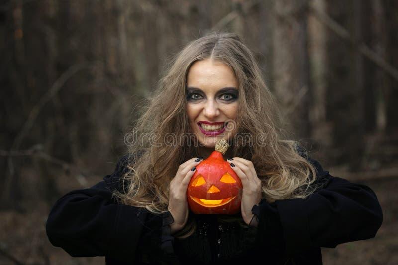 Veille de la toussaint belle fille avec un potiron dans une robe noire dans la forêt photographie stock libre de droits
