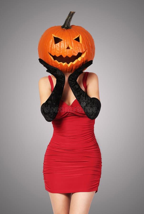 Veille de la toussaint Dame sexy en rouge avec le grand potiron sur la tête photos libres de droits