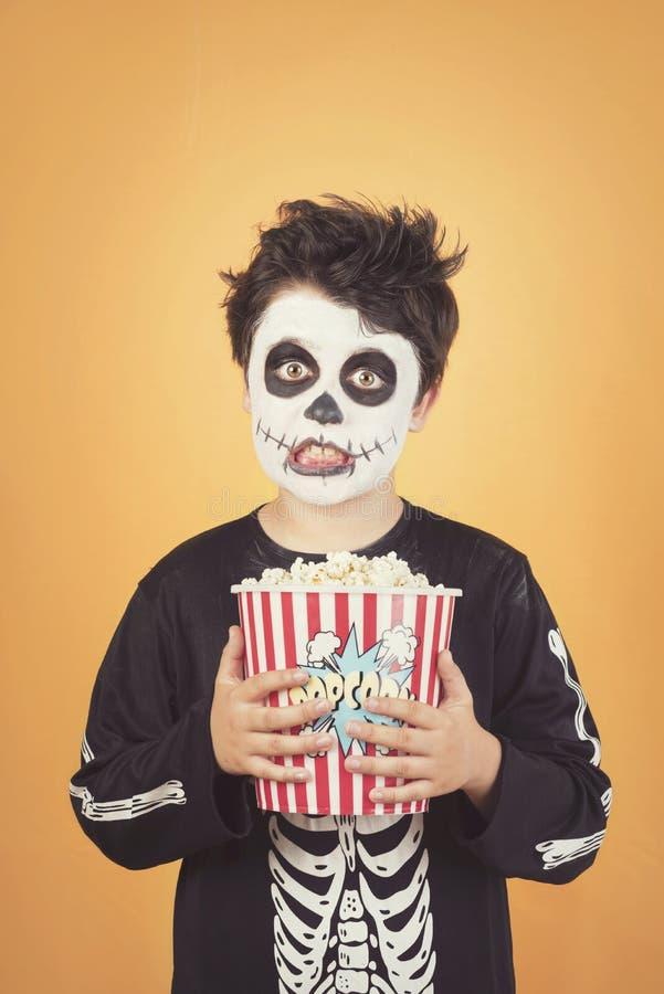Veille de la toussaint heureuse enfant drôle dans un costume squelettique avec le maïs éclaté image libre de droits