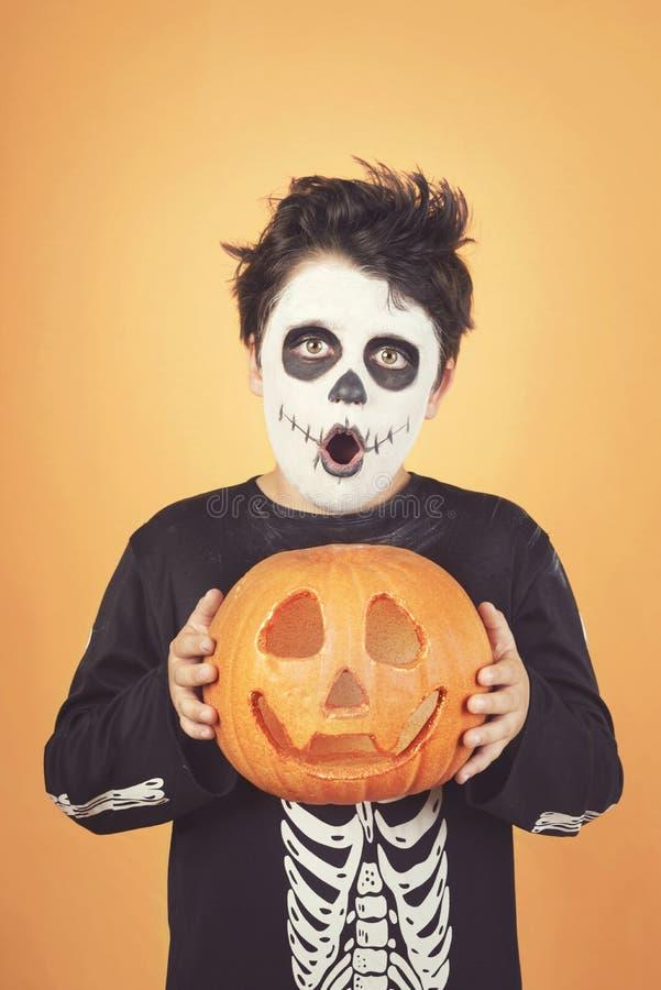 Veille de la toussaint heureuse enfant drôle dans un costume squelettique avec le potiron de Halloween plus de sur sa tête images stock