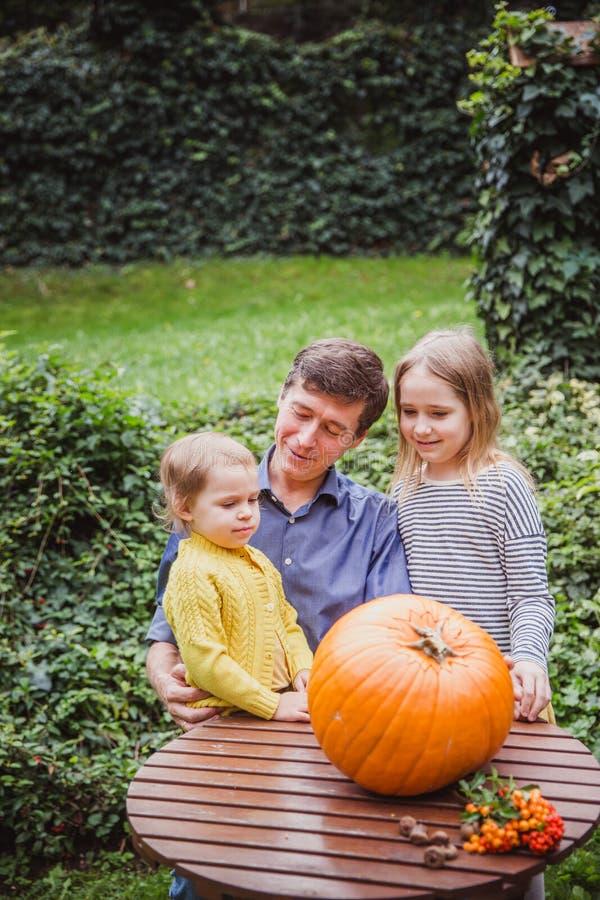 Veille de la toussaint heureuse Le père et deux filles regardent le visage coupé dans le potiron pour Halloween dehors photos stock