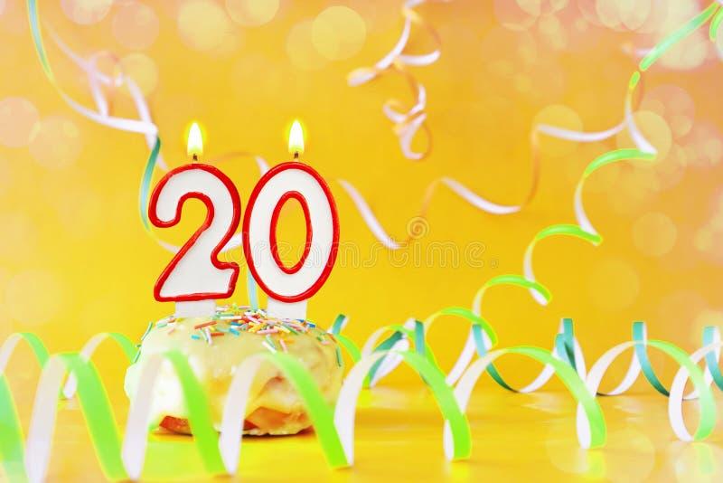 Veinte años de cumpleaños Magdalena con las velas ardientes bajo la forma de número 20 imagenes de archivo