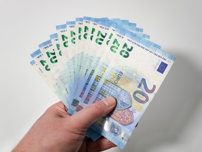 Veinte billetes de banco euro avivados hacia fuera en la mano de un varón caucásico contra el fondo blanco dinero europeo imagen de archivo libre de regalías