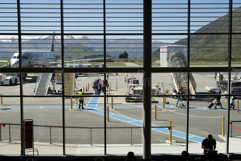 Veiw por dentro del aeropuerto de Queenstown de los pasajeros que caminan a través de pista de un avión de Jetstar foto de archivo libre de regalías