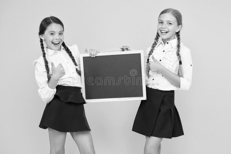 Veja isto Meninas de escola alunos bonitos ocupam espaço na cópia do quadro Fundo amarelo da equipe de iniciativa Classmates Ingr imagem de stock