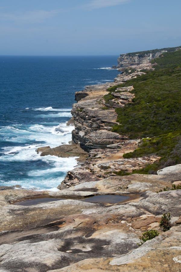 Veja penhascos ásperos ao longo do litoral no parque nacional real foto de stock