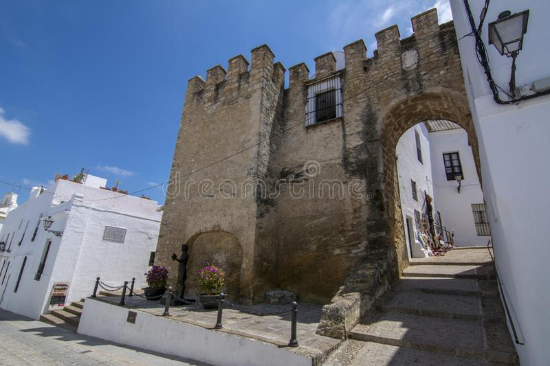 Old city wall with gate of Vejer de la Frontera in Spain. Vejer de la Frontera, Andalucia, Spain, July 2017: Part of the castle wall battlements of Vejer de la stock image