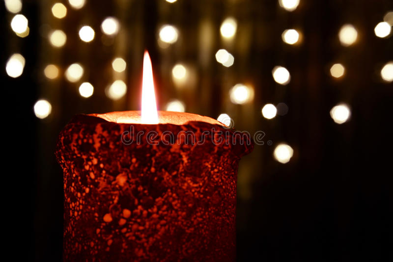 Vela alaranjada sobre luzes de Natal fotos de stock royalty free