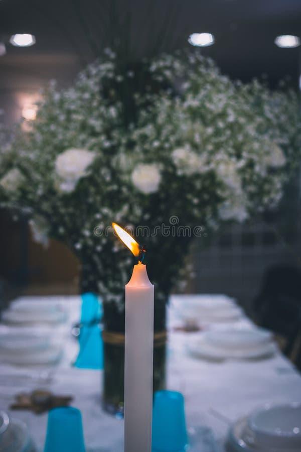 Vela alta blanca en la tabla de cena con las flores borrosas blancas en el fondo imagen de archivo