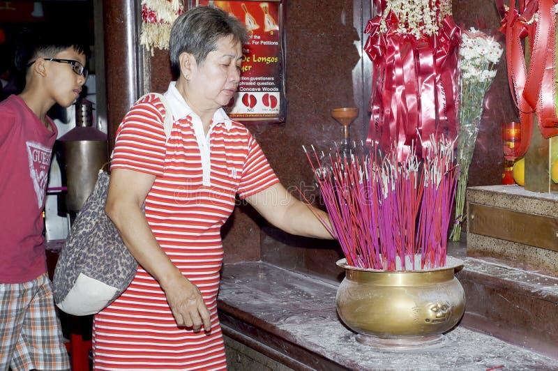 Vela amadurecida da luz da mulher e vara de Joss a rezar para parentes partidos no templo chinês em Manila imagens de stock royalty free