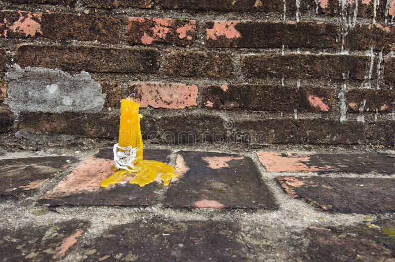 Vela amarilla delante de la pared de ladrillo marrón fotos de archivo