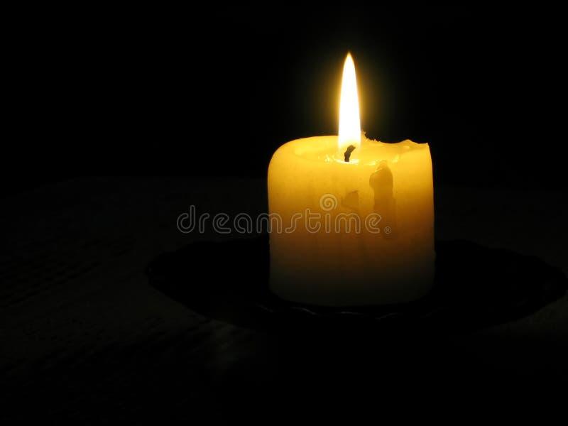 Vela amarilla en un cuarto oscuro fotografía de archivo libre de regalías