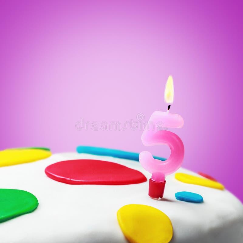 Vela ardente com o número cinco em um bolo de aniversário imagem de stock royalty free