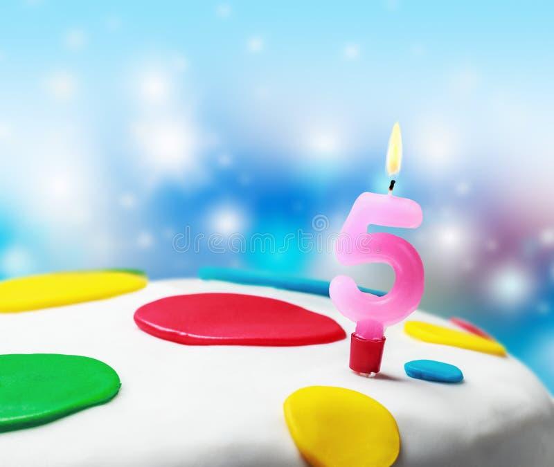 Vela ardente com o número cinco em um bolo de aniversário imagem de stock