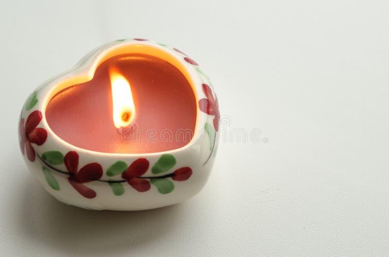 Vela ardente decorativa na forma de um coração fotos de stock royalty free