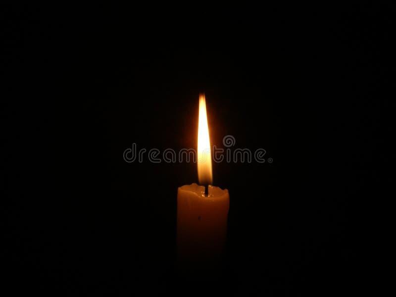 Vela ardente na escuridão foto de stock