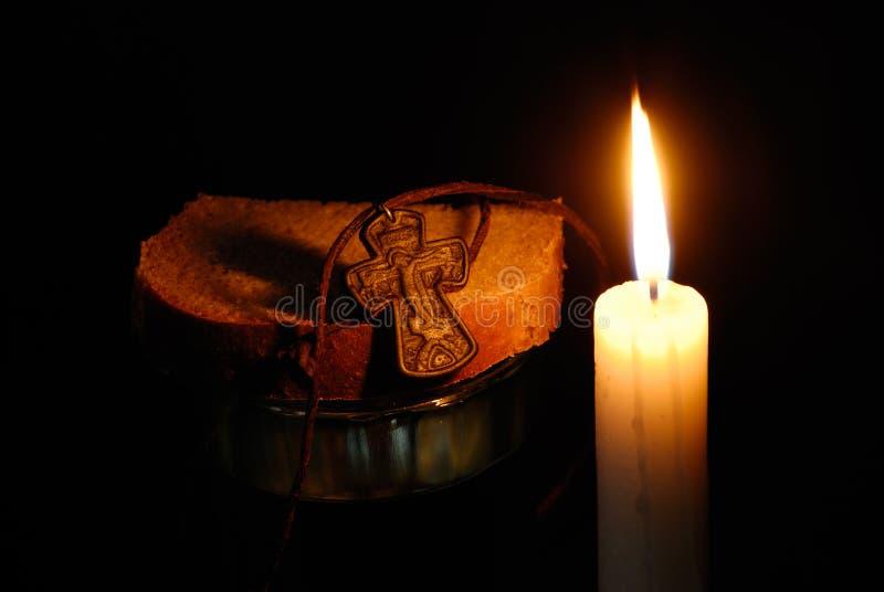Vela ardente, rood, vidro com água e pães imagem de stock royalty free