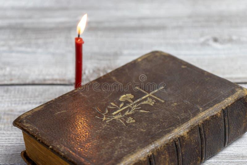 Vela ardiendo de la biblia católica y de la iglesia roja en fondo de madera imagenes de archivo