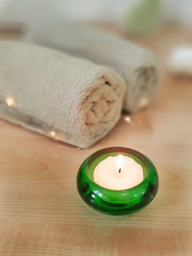 Vela ardiendo en el vidrio verde, toallas en la tabla de madera fotografía de archivo libre de regalías