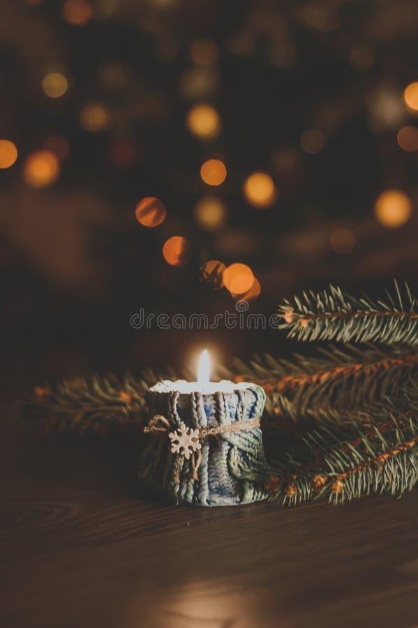 Vela ardiendo en una palmatoria acogedora con un copo de nieve en el th imagen de archivo